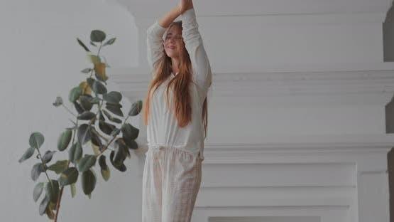 Schönes Mädchen genießt Musik in einem hellen Raum, der im Pyjama tanzt