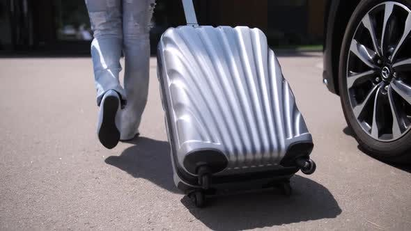 Thumbnail for Legs of Woman Carrying Suitcase Walking From Car
