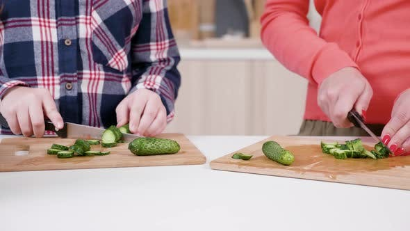Daughter Helping Mother To Cut Cucumbers at the Kitchen