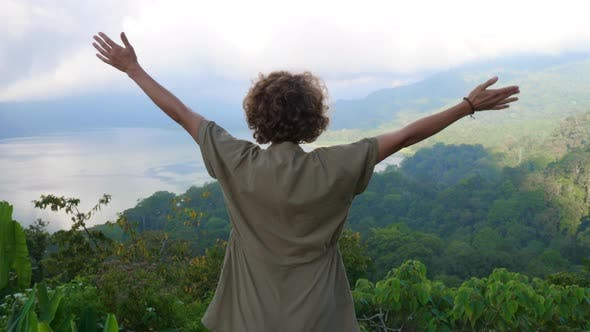 Back View of a Woman Spreading Her Arms Wide on High Mountain Point with a View of Batur Lake