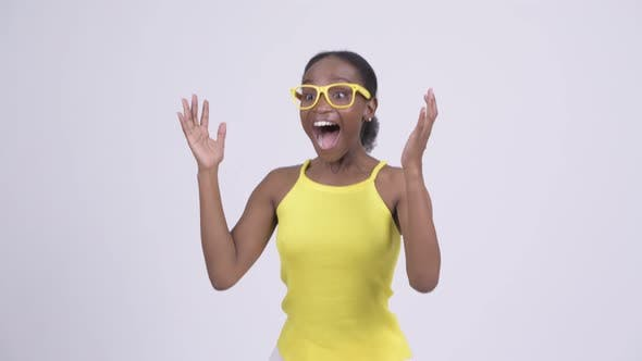 Thumbnail for Happy Young African Woman Looking Surprised and Waving Hand