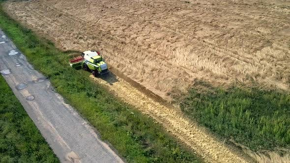 Thumbnail for Flycam Rises Over Harvester Working in Gold Wheat Field