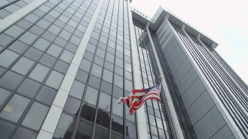 Low Angle Shot of an American Flag Waving in Front of a Skyscraper
