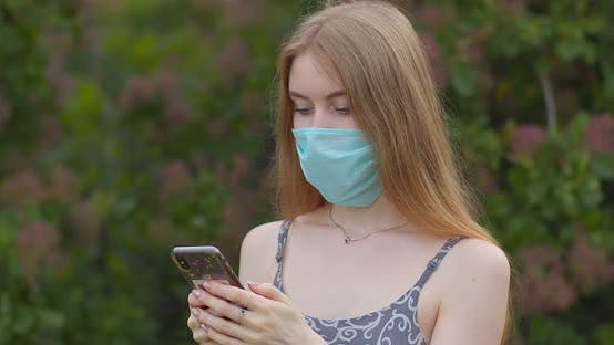 Thumbnail for A young girl in a protective medical mask looks at the phone and sends messages