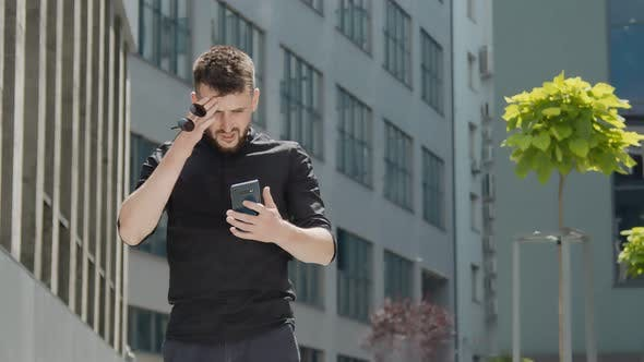 Young Businessman Who Received Bad News Through a Message on a Smartphone. Frustrated Young Man.