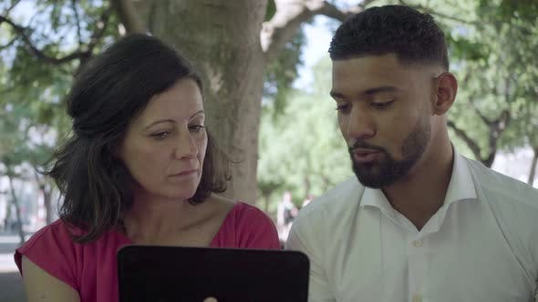 Thumbnail for Focused Employees Looking at Tablet and Talking Outdoor