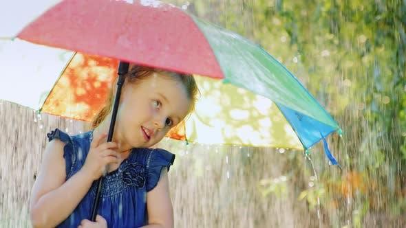 Thumbnail for Funny Girl Hiding Under an Umbrella From the Rain. Warm Summer Rain