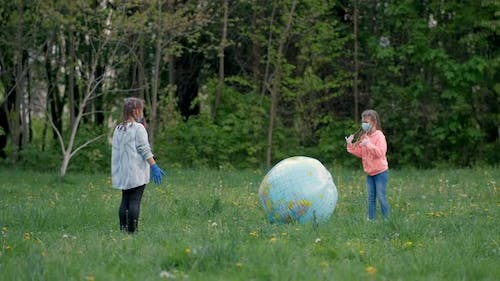 Two Girls in Medical Masks Play with a Large Inflatable Ball in the Park in the Spring. The Concept