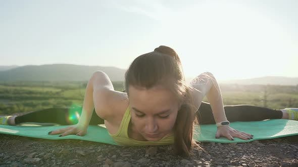 Cover Image for Sport Girl on the Top of Mountain Performs the Stretching