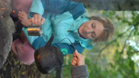 Thumbnail for Two Female Friends Make Coffee in a Kettle on an Open Fire in the Forest, A Vertical Video