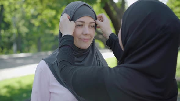 Thumbnail for Unrecognizable Woman Adjusting Hijab of Smiling Young Beautiful Lady Outdoors. Portrait of Confident