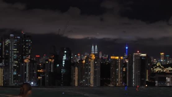 Thumbnail for Ansicht der Frau schwimmt im Pool auf dem Wolkenkratzerdach und dann auf Nacht Stadt Landschaft beobachten