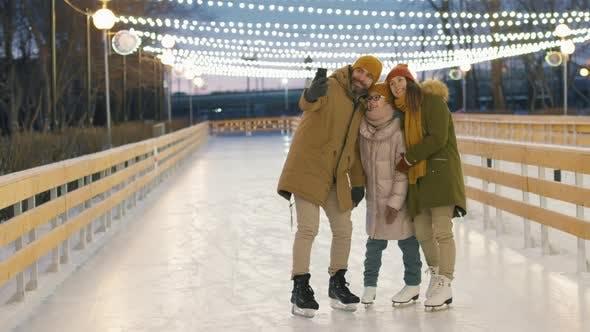 Familie nimmt Selfie auf der Eisbahn