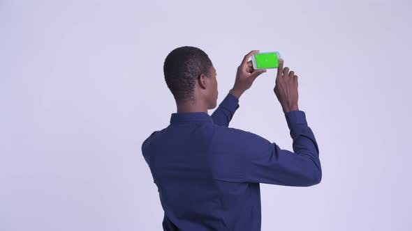 Cover Image for Rear View of Young Happy African Businessman Taking Picture with Phone