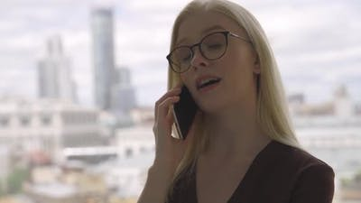 Confident Business Woman with Glasses Talking on the Phone with Her Business Partner Near a Large