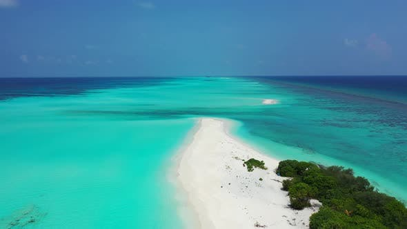 Wide angle aerial travel shot of a sandy white paradise beach and aqua turquoise water background in