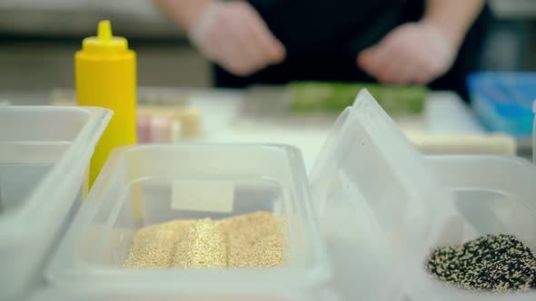 Defocused, CU: Cook Prepares a Japanese Roll with Rice and Sesame Seeds.