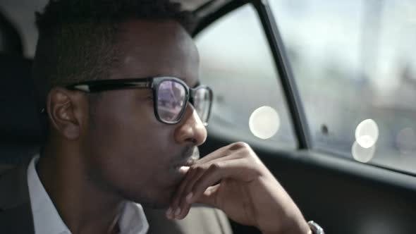 Thumbnail for African Businessman Watching Road during Car Trip