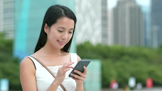 Thumbnail for Young woman use the app on cellphone in city
