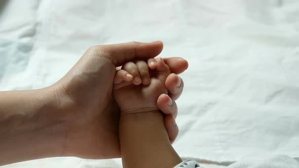 Thumbnail for Parent Hands Holding Newborn Baby Fingers