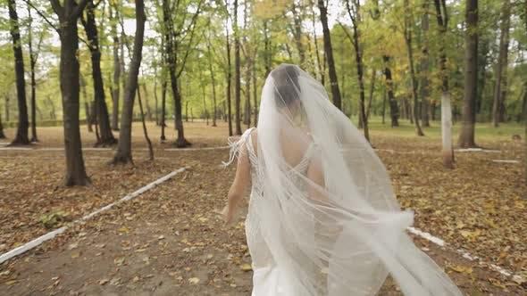 Thumbnail for Schöne und schöne Braut im Hochzeitskleid Laufen im Park. Zeitlupe
