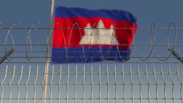 Cover Image for Waving Flag of Cambodia Behind Barbed Wire Fence