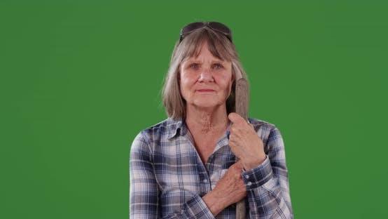 Thumbnail for Stern Senior Frau mit Gartenwerkzeug vor grünem Composite-Schlüssel