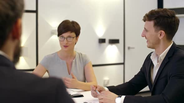 Thumbnail for Smiling Business Partners Having Discussion at Meeting Table