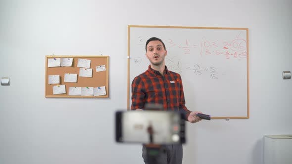 Young Teacher Teaching Remotely Using Smartphone Camera To Stream Lesson