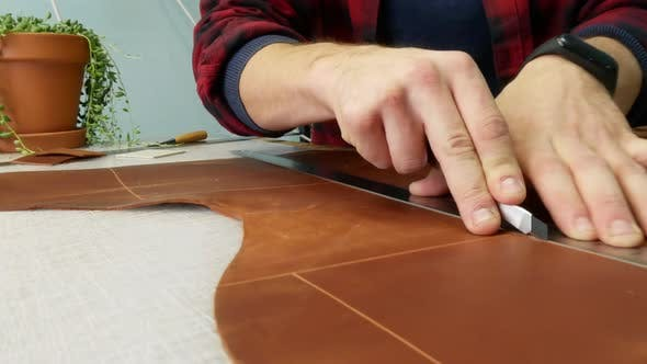 Thumbnail for Man Hand Leather Worker Cuts Off Extra Piece of Leather with an Utility Knife. Close Up