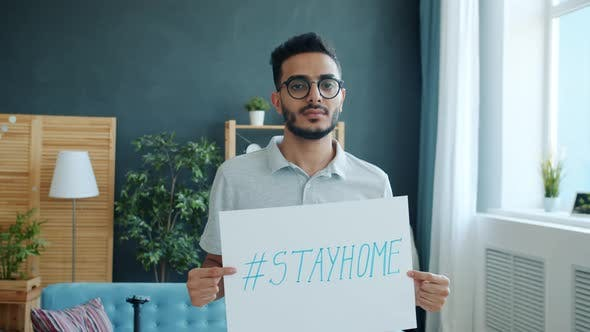 Portrait of Middle Eastern Man Holding Stayhome Banner in Apartment During Infection Outbreak and
