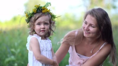 Happy Mother and Daughter with the Flower Wreath