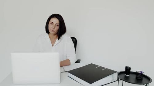 Female Teacher Conducts an Online Lecture on a Laptop on Background in Office