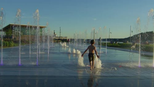 Happy kid playing at Fontaine Du Quai Paquet