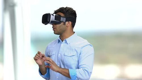 Portrait of Young Scared Man Using Virtual Reality Glasses.