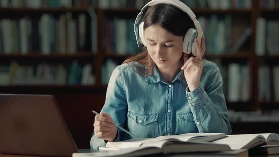 Thumbnail for Female Student in Earphones Reading in Library