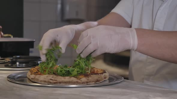 Thumbnail for Closeup of Male Hands in Gloves Adding Greenery on Pizza in Restaurant Kitchen