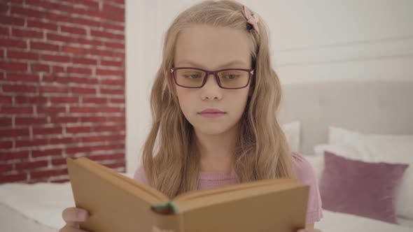 Thumbnail for Young Intelligent Teenage Girl in Glasses Reading the Book at Home