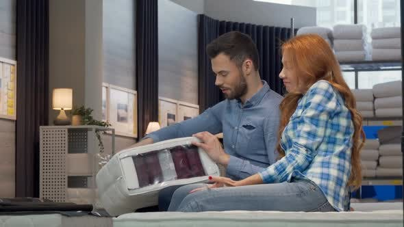 Thumbnail for Couple Choosing Orthopedic Mattress at Furniture Store Together