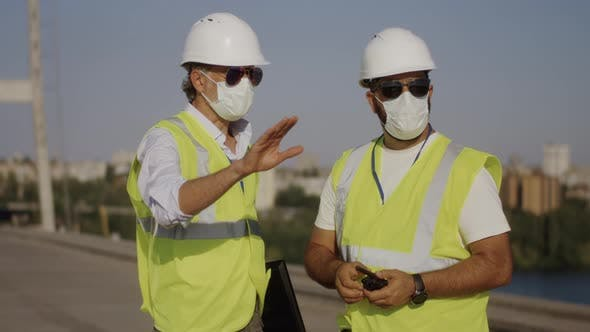 Contactors in Masks Talking on Construction Site