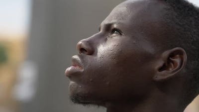 close up on hope, optimism for the future.Young black man looking up