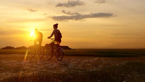 Thumbnail for Couple Wandering with Bicycles at Sunset