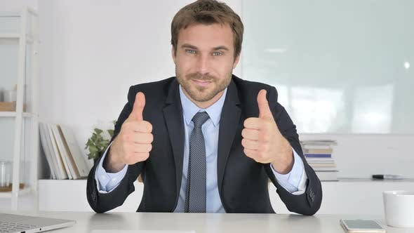 Thumbnail for Thumbs Up By Businessman Looking at Camera in Office