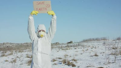 Man Wore in Protective Suit Raises Save Earth Sign on Abandoned Place in Winter
