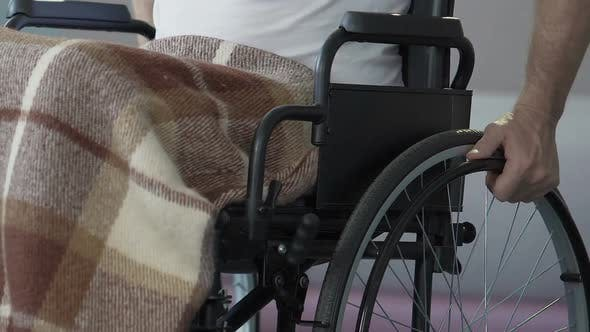 Thumbnail for Man in wheelchair starting to push it by hands post-injury rehabilitation course
