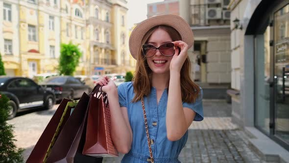 Thumbnail for Young Woman with Shopping Bags Walking in a City at Summer Day