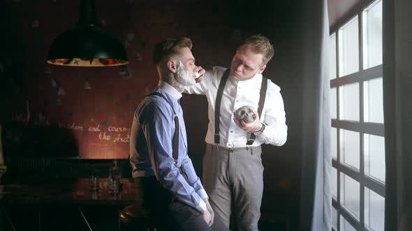 Thumbnail for Tattooed Barber Applies Foam By Shaving Brush on Face of His Tattooed Client, Barber Shop in 30's