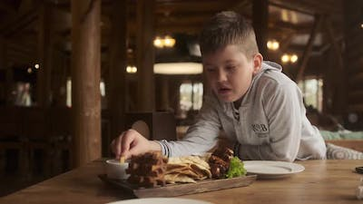 boy sits at table in restaurant and eats French fries. Boy soaks potatoes in red ketchup