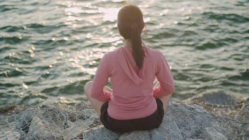 Asian athletic female meditating sitting on stones seaside while beautiful sunset.