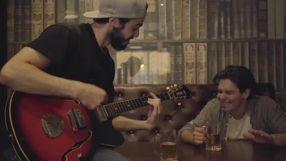 Thumbnail for Young Positive Bearded Man Playing Guitar in the Bar, His Male Friend Sitting Near Shaking His Head